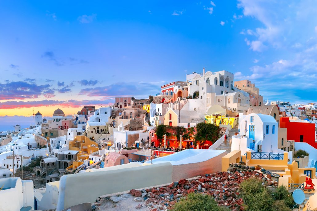 Old Town of Oia or Ia on the island Santorini, white houses, windmills and church with blue domes at sunset, Greece-min