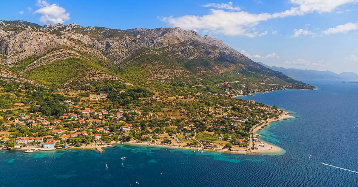 Helicopter aerial shoot of sandy beach Zrnovo near Orebic on Peljesac peninsula, Croatia. World known surfers destination